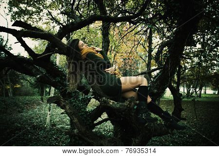 young woman wearing yellow wool csarf and green dress rest on tree in park full body shot, autumn winter fashion