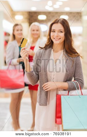 sale, consumerism, money and people concept - happy young women with shopping bags and credit card in mall