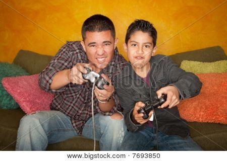 Hispanic Man And Boy Playing Video Game