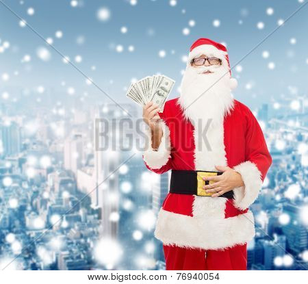 christmas, holidays, winning, currency and people concept - man in costume of santa claus with dollar money over snowy city background
