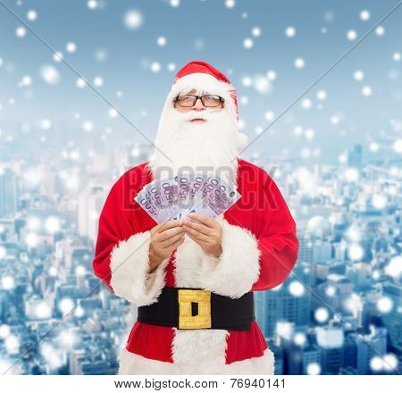 christmas, holidays, winning, currency and people concept - man in costume of santa claus with euro money over snowy city background