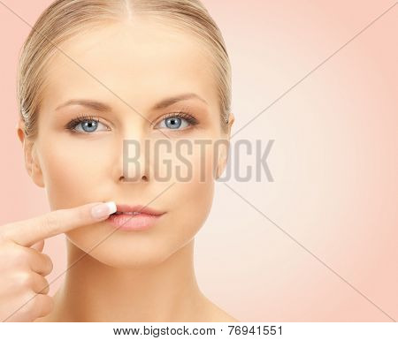 beauty, people and health concept - beautiful young woman pointing finger to her lips over pink background