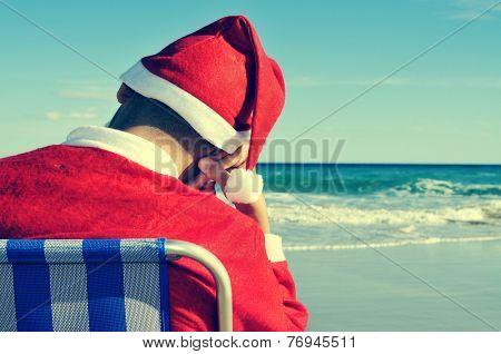 santa claus taking a nap in a beach chair on the beach