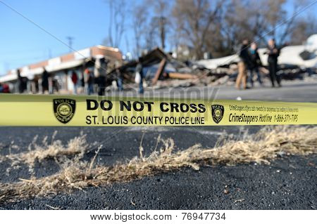 FERGUSON, MO/USA - NOVEMBER 25, 2014: Police yellow tape in front of smoldering remains of Prime Beauty Supply in Ferguson in the aftermath of riots.