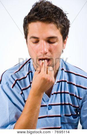 Young Man Taking Pills