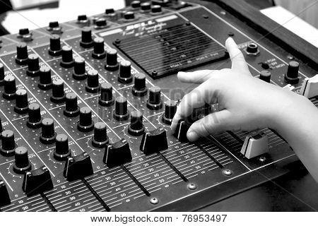Audio sound mixer and child`s hand black and white