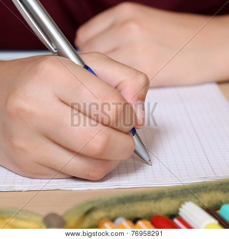 Student Writing With Hand In His Exercise Book At School