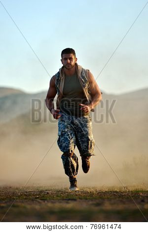 athletic young man exercising outdoor on dusty field