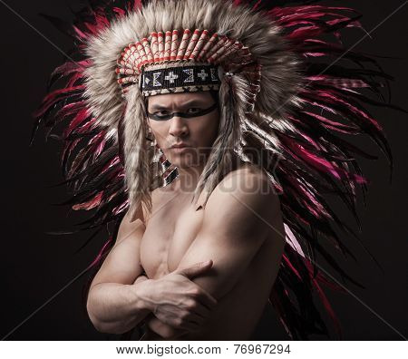 Indian strong man posing with traditional native american make up