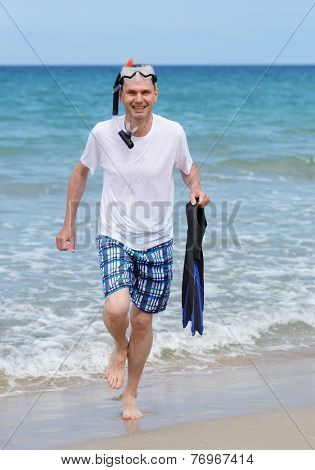 Man with mask, flippers, and snorkel against a sea