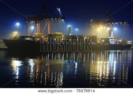 the cargo ship is unloaded in the night port