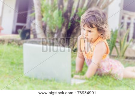 young child girl watch movie on laptop on green natural background