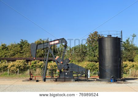 Oil Pump Jack (Sucker Rod Beam) and Reserve Tank on Sunny Day