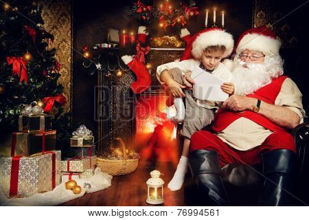 Little boy and Santa Claus reading letters from children. They are at home, decorated for Christmas. Santa's mail.