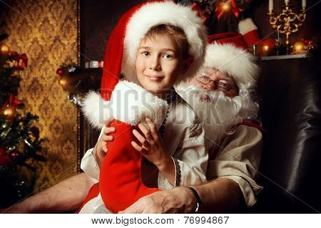 Santa Claus in his everyday clothes in Christmas home d�?�©cor. Happy little boy helps Santa Claus get ready for Christmas.