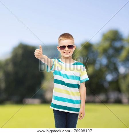 happiness, summer, childhood, gesture and people concept - smiling cute little boy in sunglasses over park background showing thumbs up