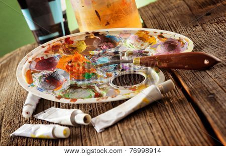 Professional acrylics paints with artistic putty knife on wooden board