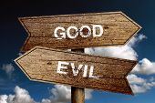 stock photo of good-vs-evil  - Good Or Evil concept road sign with blue sky background - JPG