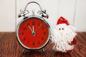 stock photo of father time  - Santa Claus or Father Frost and vintage alarm clock with red dial on wooden background. Showing time five minutes before twelve midnight