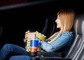 foto of watching movie  - Side view of smiling woman holding snacks while watching movie at cinema theater - JPG