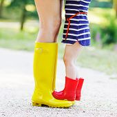 foto of woman boots  - Young mother and little adorable child girl in rubber boots having fun together family look in summer park on sunny warm day - JPG
