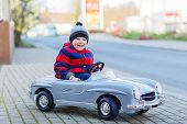 image of little kids  - Happy little boy driving big vintage old toy car and having fun outdoors - JPG