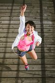 foto of manga  - Successful young sporty woman jumping with arm up - JPG