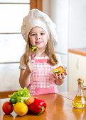 stock photo of cook eating  - child girl in cook hat eating food vegetables - JPG