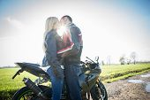 stock photo of biker  - Couple of lovers kissing with motorbike in the background  - JPG