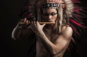pic of headdress  - Portrait of the naked indian strong man posing with traditional native american make up with flute and headdress looking at the camera - JPG