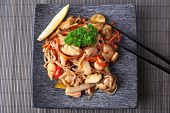 stock photo of chinese parsley  - Chinese noodles with vegetables and seafood on plate on bamboo mat background - JPG