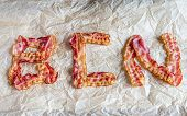 foto of bacon strips  - Fried Bacon Strips Put In Letters On The Baking Paper - JPG