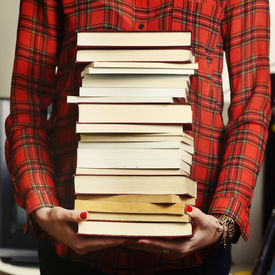 stock photo of librarian  - Woman holding a pile of books for studying concept - JPG