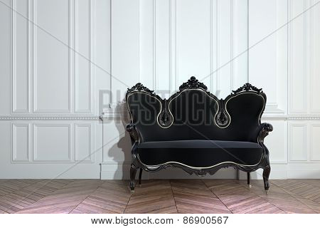 Black vintage ornately carved wooden couch against a white paneled wall on a bare parquet floor with herringbone pattern in a class house interior. 3d Rendering