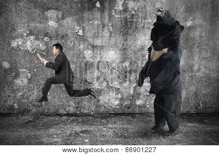 Businessman Holding Tablet Running From An Angry Bear