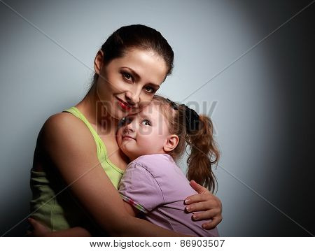 Young Mother And Happy Daughter Cuddling On Dark