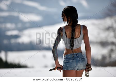 Attractive sensual woman in shorts holding knife outdoor in winter