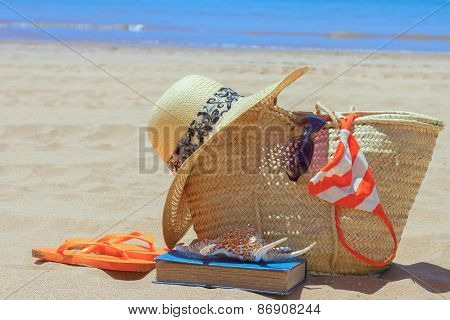 sunbathing accessories on sandy beach in straw bag