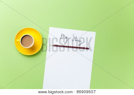 Yellow Cup Of Coffee With Paper And Pencil