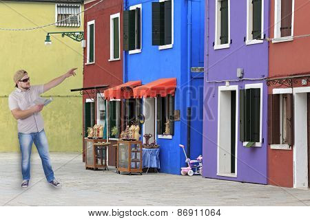 Man with guide book in a hand with houses with coloured facades, Burano, Venice, Itlaly