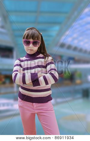 Teenage girl in pink wears sunglasses with modern shopping mall in background