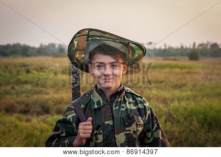 Young smiling boy with hunting shotgun standing at green field