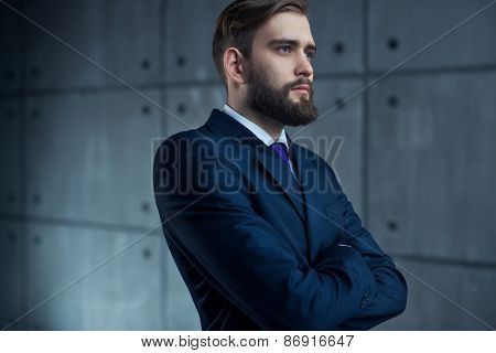 Young handsome man with beard in black suit looking outside to window.