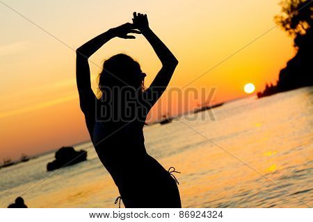 silhouette of young beautiful woman on tropical sunset sea background