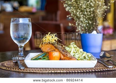 table setup in outdoor cafe, small restaurant in a hotel, summer vacations, meal time, grilled salmon with pasta and vegetables