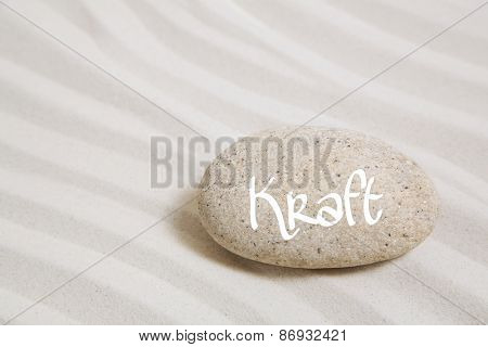 Stone in the sand with the german word power. Idea background for wellness and mental therapy.