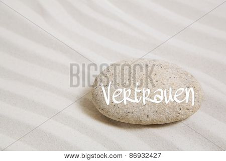 Sand background with a stone and the german word for trust.
