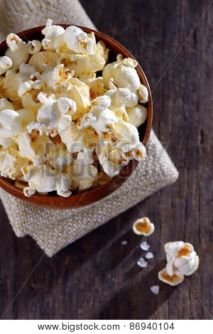 Pop corn in a bowl on a wooden table