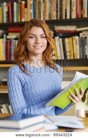 people, knowledge, education and school concept - happy student girl reading books in library