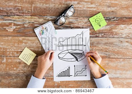 business, education, planning, strategy and people concept - close up of hands drawing charts and chart on paper sheets at table